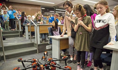 A class of girls observing robots